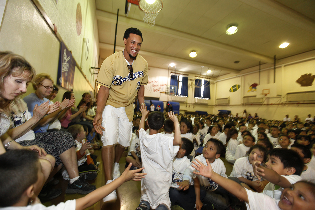 Carlos Gomez high fives the kids