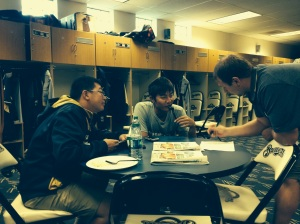 Wei-Chung Wang getting help filling out NCAA bracket from interpreter Jay Hsu and clubhouse attendant Ben Wilkes.