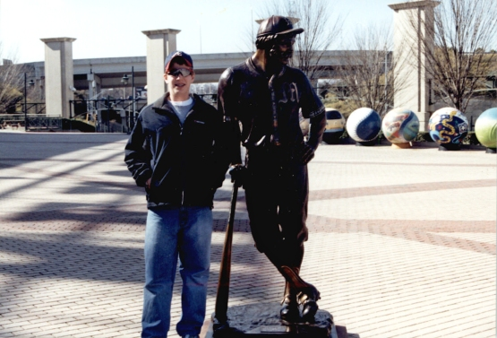 "A young Will poses next to a statue of ""Mighty Casey"" at Turner Field. (The statue is no longer there.)"