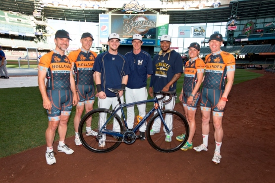 Scooter Gennett, Craig Counsell and Jeremy Jeffress pose with folks from the Lowlands Group--and the bike that fans who raise $500 or more can be entered to win.