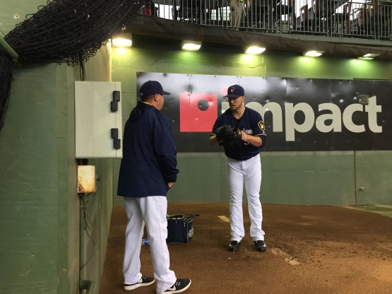 Pitching Coach Derek Johnson works with Jimmy Nelson in the bullpen between starts.