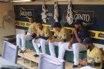 Players gather in the dugout before the game, looking good in gold!